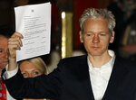 FILE - In this Thursday, Dec. 16, 2010 file photo, WikiLeaks founder Julian Assange holds up a court document for the media after he was released on bail, outside the High Court, London. (AP Photo/Kirsty Wigglesworth, file)