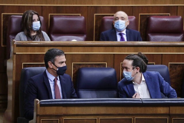 Prime Minister Pedro Sanchez, left and 2nd deputy Prime Minister Pablo Iglesias talk during a parliamentary session in Madrid, Spain, Wednesday Oct. 21, 2020. Spanish Prime Minister Pedro Sanchez faces a no confidence vote in Parliament put forth by the far right opposition party VOX. (AP Photo/Manu Fernandez, Pool)