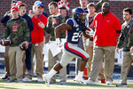 Sideline visitors react to a 30-yard touchdown run by Mississippi running back Snoop Conner (24) against New Mexico State during the first half of an NCAA college football game in Oxford, Miss., Saturday, Nov. 9, 2019. (AP Photo/Rogelio V. Solis)