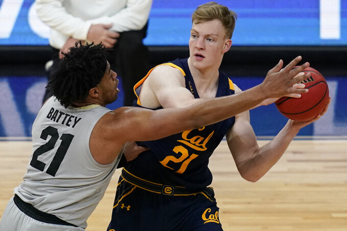 California's Lars Thiemann (21) looks to pass around Colorado's Evan Battey (21) during the first half of an NCAA college basketball game in the quarterfinal round of the Pac-12 men's tournament Thursday, March 11, 2021, in Las Vegas. (AP Photo/John Locher)