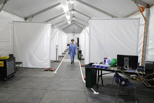 Forest Gauthier, an emergency services medical assistant, walks through a tent set up outside the Emergency Department at the Harborview Medical Center before it opened for patients, Thursday, April 2, 2020, in Seattle. The tent, which was recently put in place, is used to examine walk-up and other patients who arrive at the emergency room with respiratory symptoms possibly related to the new coronavirus. (AP Photo/Ted S. Warren)