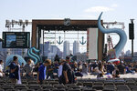 Fans take their seats Wednesday, July 21, 2021, near the stage in a Seattle park before the Seattle Kraken NHL hockey team's expansion draft event. (AP Photo/Ted S. Warren)