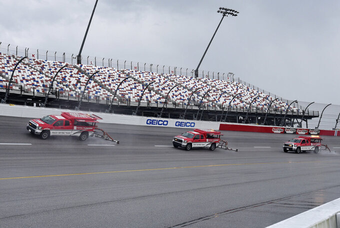 Crews try to dry the track after a rain shower before a NASCAR Cup Series auto race Sunday, Sept. 1, 2019, at Darlington Raceway in Darlington, S.C. (AP Photo/Richard Shiro)
