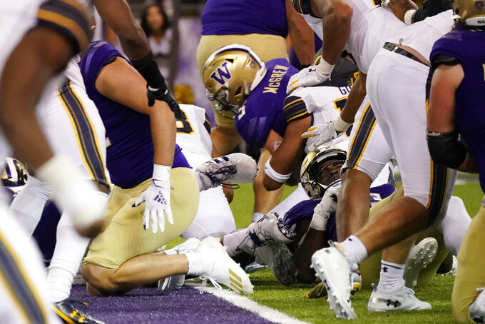 Washington's Sean McGrew carries to score a touchdown against California in overtime in an NCAA college football game Saturday, Sept. 25, 2021, in Seattle. Washington won 31-24 in overtime. (AP Photo/Elaine Thompson)