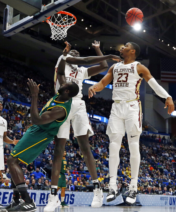 Florida State's Christ Koumadje (21) blocks a shot by Vermont's Samuel Dingba, left, as Florida State's M.J. Walker (23) looks on during the second half of a first round men's college basketball game in the NCAA Tournament, Thursday, March 21, 2019, in Hartford, Conn. (AP Photo/Elise Amendola)