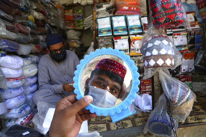 FILE - In this Thursday, April 8, 2021, file photo, a man tries on a traditional cap in preparation for the upcoming Muslim fasting month of Ramadan, in Peshawar, Pakistan. Muslims are facing their second Ramadan in the shadow of the pandemic. Many Muslim majority countries have been hit by an intense new coronavirus wave. While some countries imposed new Ramadan restrictions, concern is high that the month's rituals could stoke a further surge. (AP Photo/Muhammad Sajjad, File)