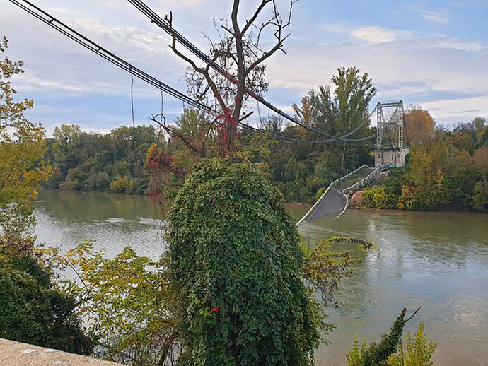 The road suspension bridge linking the towns of Mirepoix-sur-Tarn and Bessieres, after it collapsed with several vehicles into the Tarn river about 30 kilometres (18 miles) north of the city of Toulouse, in southwest France, Monday Nov. 18, 2019.  One 15-year old girl is confirmed dead, and four people were rescued, but several others are feared missing, after the collapse of the bridge the fire service said. (Olivier Le Corre via AP)
