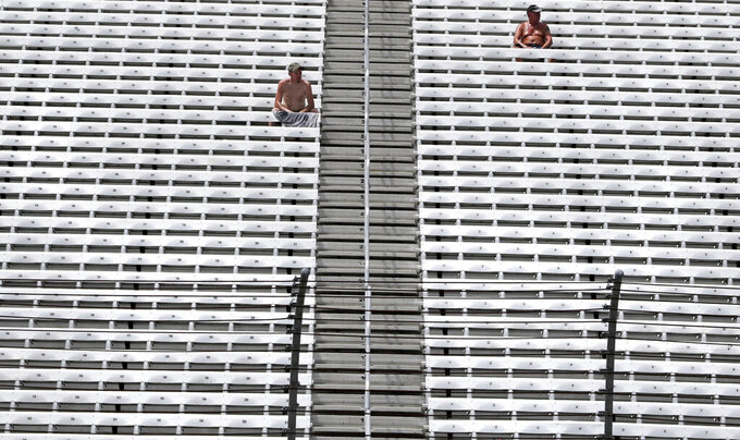 Two shirtless men watch from nearly empty stands during a NASCAR Cup Series auto race practice at New Hampshire Motor Speedway in Loudon, N.H., Saturday, July 20, 2019. Temperatures were forecasted to reach nearly 100 degrees at the track. (AP Photo/Charles Krupa)
