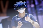 A visitor tests a VR device at the TelcoDR booth during the Mobile World Congress 2021 in Barcelona, Spain, Monday, June, 28, 2021. The Mobile World Congress takes places in Barcelona from June 28 to July 1. (AP Photo/Bernat Armangue)