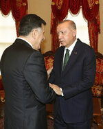Turkey's President Recep Tayyip Erdogan, right, shakes hands with Fayez al Sarraj, the head of Libya's internationally-recognized government, prior to their meeting in Istanbul, Sunday, Jan. 12, 2020. The meeting at Dolmabahce Palace took place on the first day of a ceasefire in Libya initiated by Turkey and Russia. (Turkish Presidency via AP, Pool)
