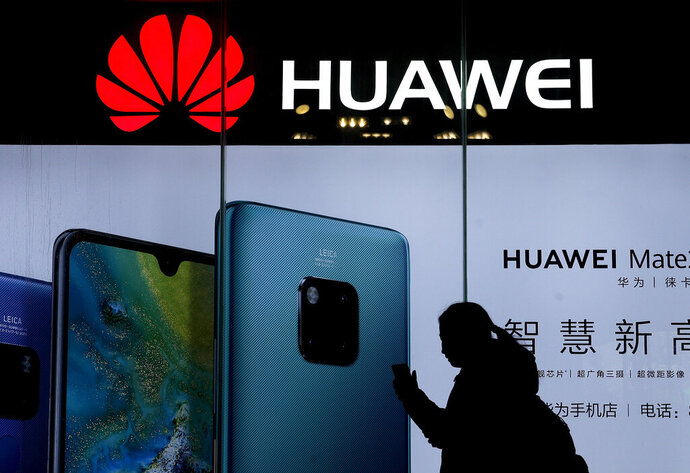 FILE - In this Dec. 11, 2018, file photo, a woman browses her smartphone as she walks by a Huawei store at a shopping mall in Beijing. China's government has accused Washington of trying to block its industrial development after Vice President Mike Pence said Chinese tech giant Huawei and other telecom equipment suppliers are a security threat. (AP Photo/Andy Wong)