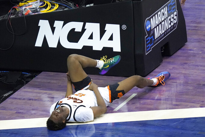 Oklahoma State forward Matthew-Alexander Moncrieffe falls to the floor in pain during the second half of a first round NCAA college basketball game Friday, March 19, 2021, at the Indiana Farmers Coliseum in Indianapolis. Alexander Moncrieffe stayed in the game as Oklahoma State won 69-60. (AP Photo/Charles Rex Arbogast)
