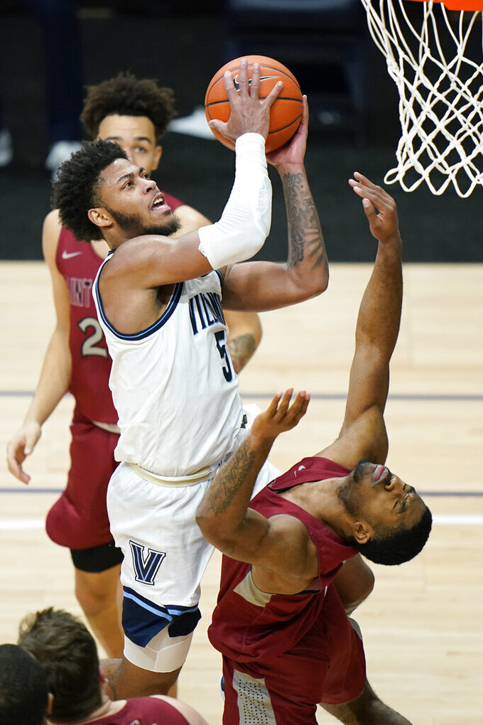 Villanova's Justin Moore, left, goes up for a shot against Saint Joseph's Rahmir Moore during the second half of an NCAA college basketball game, Saturday, Dec. 19, 2020, in Villanova, Pa. (AP Photo/Matt Slocum)