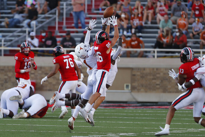 Texas Tech wide receiver Dalton Rigdon makes a catch defended by Texas defensive back Chris Adimora during the second half of an NCAA college football game against Texas Tech, Saturday Sept. 26, 2020, in Lubbock, Texas. (AP Photo/Mark Rogers)
