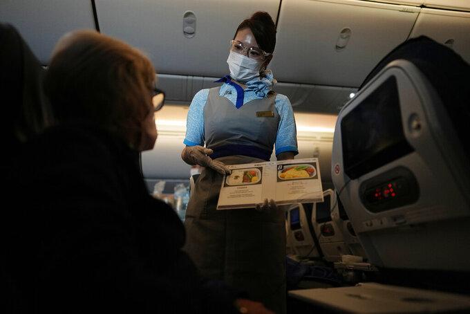 A flight attendant shows the food options on a flight to Tokyo from Frankfurt, Germany, Monday, July 19, 2021. (AP Photo/Natacha Pisarenko)