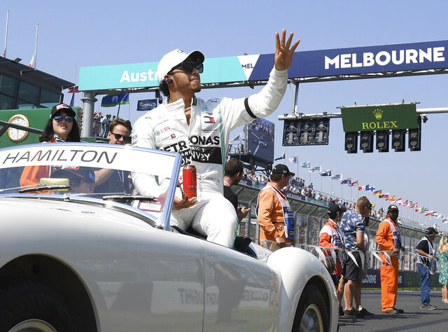 In this March 17, 2019, file photo, Mercedes driver Lewis Hamilton of Britain waves as the drivers parade begins ahead of the Australian Grand Prix in Melbourne, Australia. The start of the 2021 Formula One season has been delayed after the Australian Grand Prix was postponed because of the coronavirus pandemic. The Australian race in Melbourne has been rescheduled from March 21 to November 21. (AP Photo/Andy Brownbill, File)
