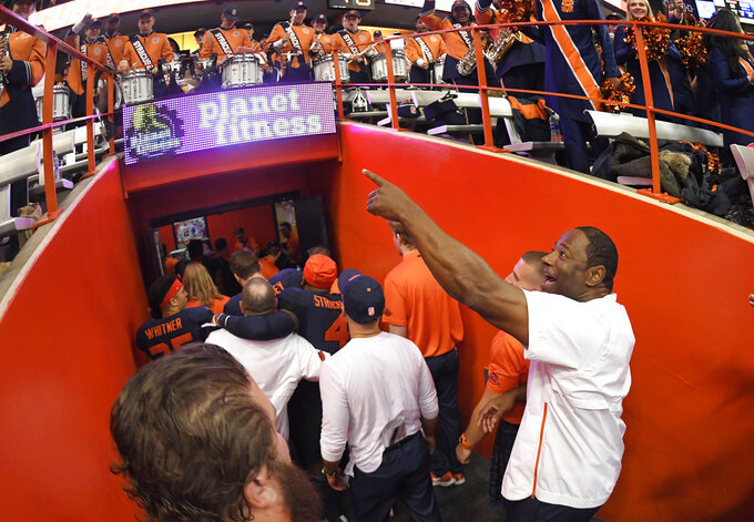 Syracuse head coach Dino Babers, right, acknowledges fans on his way to the locker room after the team's win over North Carolina State in an NCAA college football game in Syracuse, N.Y., Saturday, Oct. 27, 2018. (AP Photo/Adrian Kraus)