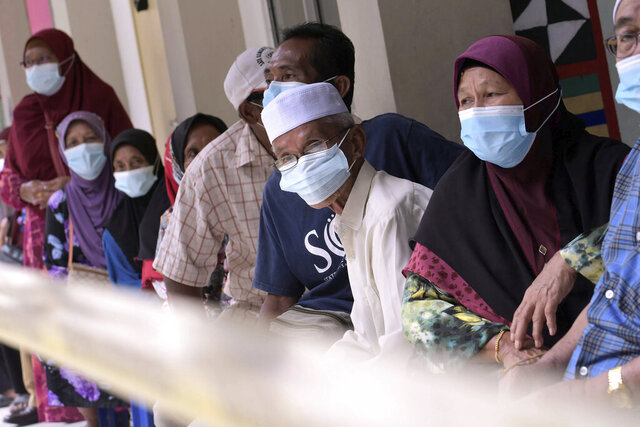 Voters wearing face masks to help curb the spread of the coronavirus wait for their turn at a polling station during a state election on the outskirts of Kota Kinabalu, in Malaysia's Sabah state on Borneo island, Saturday, Sept. 26, 2020. Polls opened Saturday in Malaysia's eastern Sabah state in a vote seen as a referendum for embattled Prime Minister Muhyiddin Yassin's 7-month-old unelected government. (AP Photo)