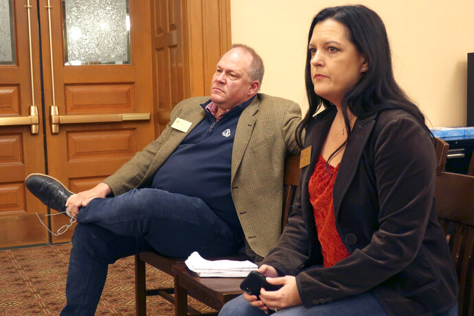 Lobbyists Scott Schneider, left, of the Kansas Restaurant and Hospitality Association, and Kristi Brown of the Kansas Chamber of Commerce, watch as a Kansas House committee debates a bill their groups support on single-use plastic bags and straws, Friday, Feb. 21, 2020, at the Statehouse in Topeka, Kan. The bill approved by the committee prohibits cities and counties from banning them for the next five years. (AP Photo/John Hanna)