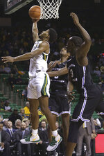Baylor guard Jared Butler (12) scores past Central Arkansas guard Masai Olowokere (5) and Central Arkansas guard Eddy Kayouloud (13), left, in the second half of an NCAA college basketball game Tuesday, Nov. 5, 2019, in Waco, Texas. (AP photo/ Jerry Larson)
