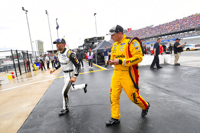 Aric Almirola, left, and Michael Mcdowell, leave the track after a NASCAR Cup series auto race was postponed until Monday due to rain Sunday, Oct. 3, 2021, in Talladega, Ala. (AP Photo/John Amis)