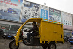 In this April 13, 2018 photo, a delivery past by a auto parts market in Beijing, China. Chinese exporters of goods from electronics to motorcycle parts are scrambling to insulate themselves from U.S. President Donald Trump's proposed tariff hike. They are weighing plans to rush shipments to American customers ahead of the increase, raise prices or find other markets. Some are looking at shipping goods through other countries to hide their Chinese origin.(AP Photo/Ng Han Guan)