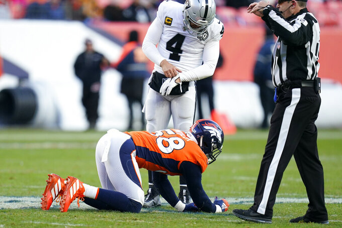 Denver Broncos outside linebacker Von Miller, below, is slow to get up after an injury as Oakland Raiders quarterback Derek Carr looks on, above, during the second half of an NFL football game Sunday, Dec. 29, 2019, in Denver. (AP Photo/Jack Dempsey)
