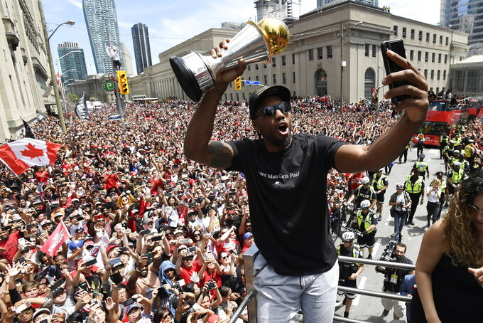 FILE - In this June 17, 2019, file photo, Toronto Raptors forward Kawhi Leonard takes a selfie holding his playoffs MVP trophy during the NBA basketball championship team's victory parade in Toronto. (Frank Gunn/The Canadian Press via AP, File)