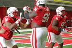 In this Aug. 7, 2019, photo, defensive lineman Carlos Davis (96), center, is flanked by brothers Darrion Daniels, left, and Damion Daniels, right, both Nebraska defensive linemen, during NCAA college football preseason practice in Lincoln, Neb. Football players often refer to their teammates as brothers. In the Big Ten, a lot of them truly are. There are more than two dozen sets of brothers playing in the conference this season. (AP Photo/Nati Harnik)