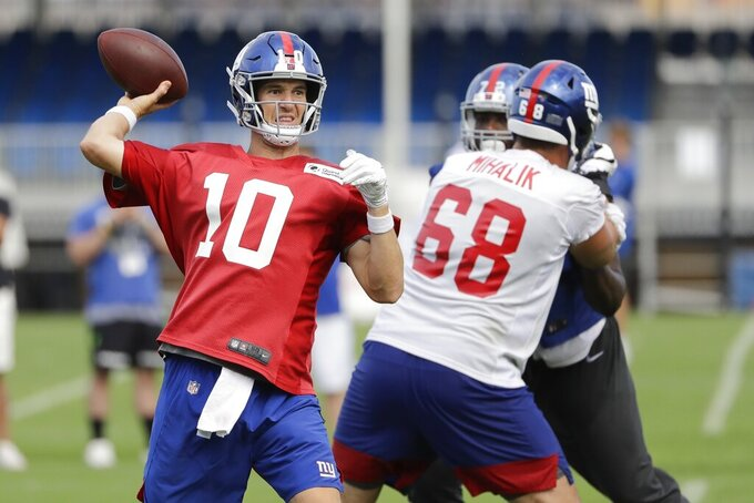 New York Giants' Eli Manning (10) throws a pass as Brian Mihalik (68) blocks during drills at the NFL football team's training camp Thursday, Aug. 1, 2019, in East Rutherford, N.J. (AP Photo/Frank Franklin II)