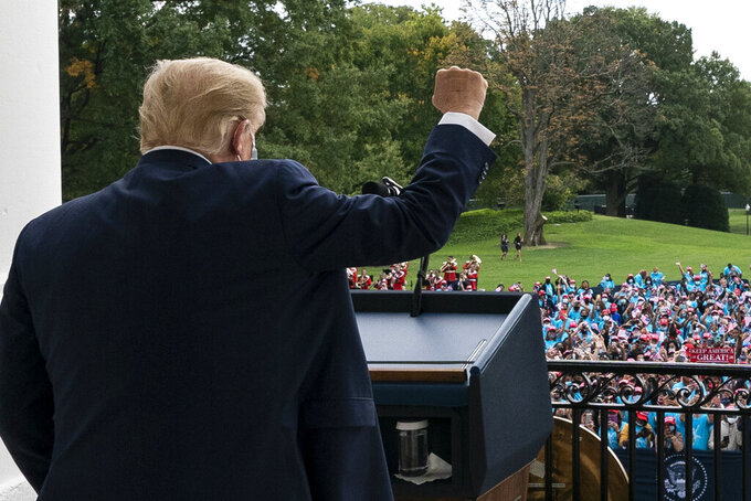 President Donald Trump pumps his fist to the crowd with a bandages on his hand, before speaking from the Blue Room Balcony of the White House to a crowd of supporters, Saturday, Oct. 10, 2020, in Washington. (AP Photo/Alex Brandon)