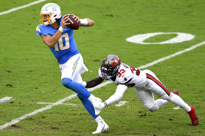 Los Angeles Chargers quarterback Justin Herbert (10) eludes a tackle by Tampa Bay Buccaneers free safety Jordan Whitehead (33) during the first half of an NFL football game Sunday, Oct. 4, 2020, in Tampa, Fla. (AP Photo/Jason Behnken)