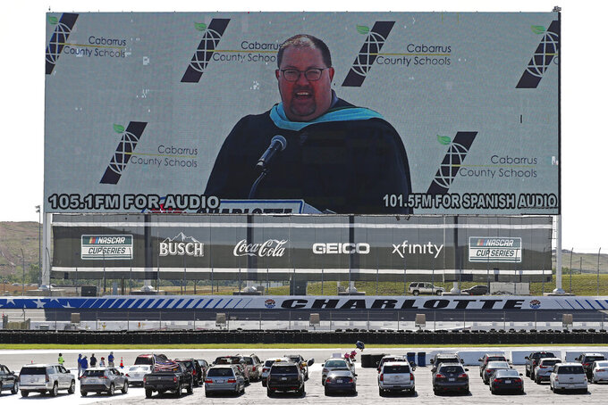 Principal Vance Fishback addresses class of 2020 graduates from Cabarrus Early College of Technology on a giant screen as they sit in cars at the Charlotte Motor Speedway during a graduation event in Concord, N.C., Friday, June 12, 2020. Due to the coronavirus pandemic Cabarrus County schools participated in a first-of-its-kind commencement ceremony for students and family. (AP Photo/Gerry Broome)