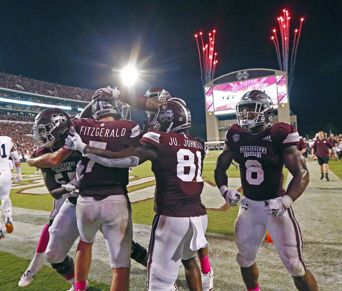 Mississippi State quarterback Nick Fitzgerald (7) and teammates celebrate his 21-yard touchdown run against Auburn as fireworks go off in the background during an NCAA college football game in Starkville, Miss., Saturday, Oct. 6 2018. Mississippi State won 23-9. (AP Photo/Rogelio V. Solis)