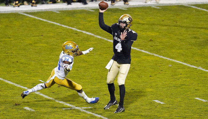 Colorado quarterback Sam Noyer, right, throws a pass under pressure from UCLA defensive back Qwuantrezz Knight in the first half of an NCAA college football game Saturday, Nov. 7, 2020, in Boulder, Colo. (AP Photo/David Zalubowski)