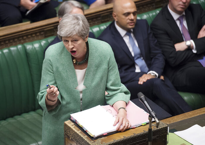 Britain's Prime Minister Theresa May speaks during Question Time inside the House of Commons in London, Wednesday July 10, 2019.   Britain's ambassador to the United States, veteran diplomat Kim Darroch resigned Wednesday, prompting Prime Minister Theresa May and other British politicians to praise Darroch. (Jessica Taylor/House of Commons via AP)