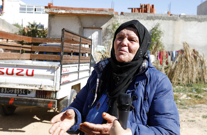 Gamra, the mother of the Nice attacker Ibrahim Issaoui gestures as she adresses reporters in Sfax, Tunisia, Friday, Oct. 30, 2020. The family of Ibrahim Issaoui expressed shock after he attacked a church in Nice and killed three people in what French and Tunisian authorities are investigating as a terrorist attack. Tunisian prosecutors say he had not been on their radar for radicalization before he fled with other migrants to the Italian island of Lampedusa in September, eventually making his way to Nice. (AP Photo/Helmy Ben Salah)