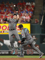 Arizona Diamondbacks shortstop Nick Ahmed, left, leaps to catch a line drive by St. Louis Cardinals' Paul DeJong for an out as Diamondbacks second baseman Eduardo Escobar watches during the sixth inning of a baseball game Friday, July 12, 2019, in St. Louis. (AP Photo/Jeff Roberson)