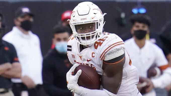 Texas outside linebacker Joseph Ossai carries during an NCAA college football game against Oklahoma State, in Stillwater, Okla., Saturday, Oct. 31, 2020. Ossai was selected to The Associated Press All-America first-team offense, Monday, Dec. 28, 2020. (AP Photo/Sue Ogrocki)