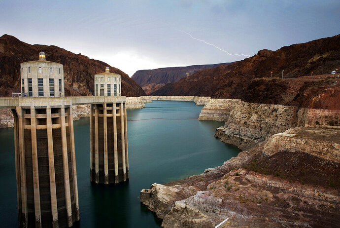 FILE - In this July 28, 2014, file photo, lightning strikes over Lake Mead near Hoover Dam that impounds Colorado River water at the Lake Mead National Recreation Area in Arizona. President Donald Trump on Tuesday, April 16, 2019, signed a plan to cut back on the use of water from the Colorado River, which serves 40 million people in the U.S. West. (AP Photo/John Locher, File)