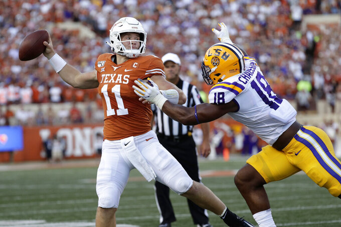 Texas quarterback Sam Ehlinger throws a pass as LSU linebacker K'Lavon Chaisson defends during the first half of an NCAA college football game Saturday, Sept. 7, 2019, in Austin, Texas. (AP Photo/Eric Gay)