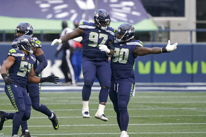 Seattle Seahawks Jarran Reed (90) and Poona Ford (97) celebrate after the New York Jets missed a field goal during the first half of an NFL football game, Sunday, Dec. 13, 2020, in Seattle. (AP Photo/Ted S. Warren)