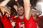 In this photo taken Oct. 1, 2019, Washington Nationals pitcher Max Scherzer, center, celebrates with teammates after winning a National League wild-card baseball game against the Milwaukee Brewers in Washington. All eyes will be on Scherzer at the World Series. And that is fitting in many ways. The Nationals star has an unusual optical condition: one eye blue, one brown. The Houston Astros, however, need only concern themselves about his arm. (AP Photo/Patrick Semansky)