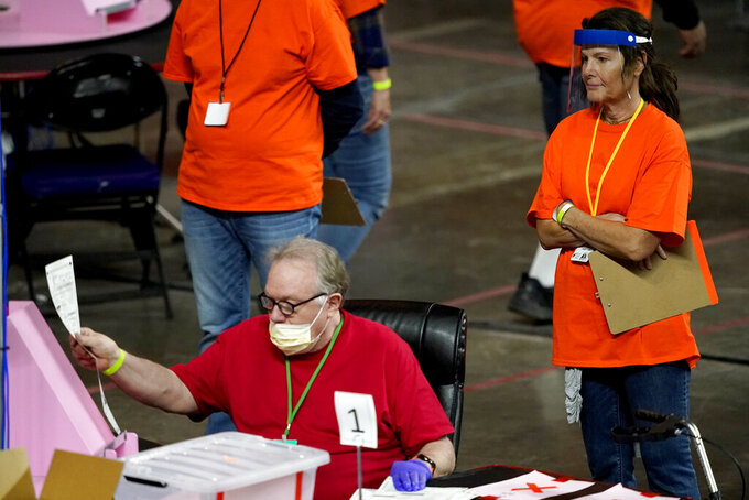 FILE - In this May 6, 2021 file photo, Maricopa County ballots cast in the 2020 general election are examined and recounted by contractors working for Florida-based company, Cyber Ninjas at Veterans Memorial Coliseum in Phoenix. For some conspiracy theorists, the 2020 election still hasn't ended. Trump supporters are pushing to re-examine ballots from November across the country, and finding success in swing states like Arizona and Georgia. Their efforts and sometimes misleading conclusions are being gleefully amplified by the former president. (AP Photo/Matt York, Pool)