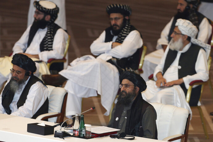 FILE - In this Sept. 12, 2020, file photo, Taliban co-founder Mullah Abdul Ghani Baradar, bottom right, speaks at the opening session of peace talks between the Afghan government and the Taliban in Doha, Qatar. After more than a month of delays, escalating violence and a flurry of diplomatic activity peace talks between the Taliban and the Afghan government have resumed Monday, Feb. 22, 2021, in the Middle Eastern State of Qatar. (AP Photo/Hussein Sayed, File)