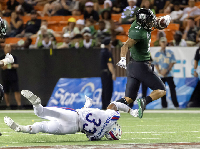Hawaii running back Fred Holly III, right, escapes the grasp of Louisiana Tech linebacker Dae'Von Washington (33) in the second half of the Hawaii Bowl NCAA college football game, Saturday, Dec. 22, 2018, in Honolulu. (AP Photo/Eugene Tanner)