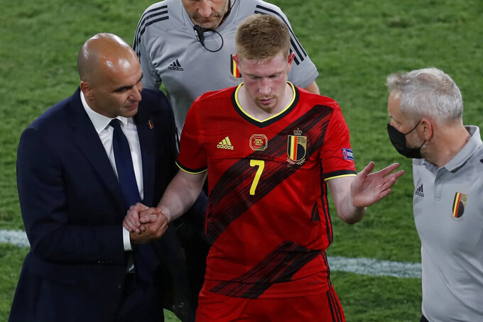 Belgium's Kevin De Bruyne leaves the match injured flanked by Belgium's manager Roberto Martine, left, during the Euro 2020 soccer championship round of 16 match between Belgium and Portugal at La Cartuja stadium in Seville, Spain, Sunday, June 27, 2021. (Jose Manuel Vidal/Pool via AP)