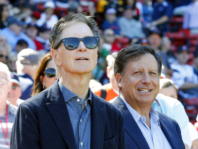 FILE - In this Sept. 27, 2015, file photo, Boston Red Sox owners John Henry, left, and Tom Werner look on before a baseball game between the Red Sox and the Baltimore Orioles in Boston. Henry and Werner intend to slash payroll to get under the luxury tax threshold next season, saying they fired Dave Dombrowski because of differing opinions on how to build for the future. The pair made their first public comments Friday, Sept. 27, 2019, since parting with Dombrowski, the president of baseball operations, on Sept. 8. (AP Photo/Michael Dwyer, File)