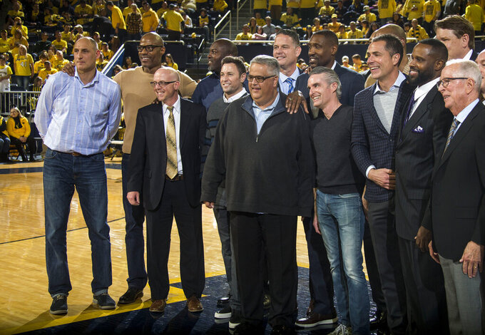Members of the 1989 Michigan basketball team and their coach Steve Fisher, far right, pose for a photo at the half of an NCAA college basketball game between Michigan and Michigan State at Crisler Center in Ann Arbor, Mich., Sunday, Feb. 24, 2019. (AP Photo/Tony Ding)