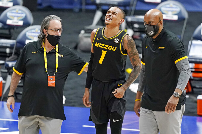 Missouri's Xavier Pinson (1) walks back to the bench with head coach Cuonzo Martin, right, after Pinson took a spill in the second half of an NCAA college basketball game against Arkansas in the Southeastern Conference Tournament Friday, March 12, 2021, in Nashville, Tenn. (AP Photo/Mark Humphrey)